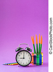 Alarm set at 9 o'clock, colorful cactus, rainbow pencils, working school drawing concept