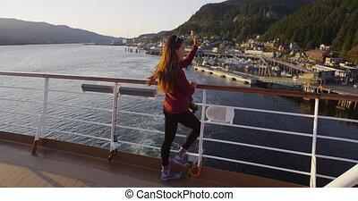 Alaska Cruise ship passenger in city of Ketchikan standing on cruise ship deck waving ashore while sailing away from Ketchikan in Inside Passage, a famous Alaska cruise ship destination.
