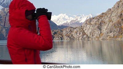 Alaska Glacier Bay cruise ship passenger looking at Alaskan mountains with binoculars exploring Glacier Bay National Park, USA. Woman on travel Inside Passage enjoying view. Focus change.