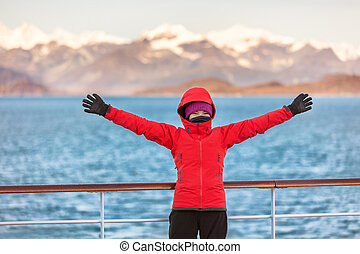 Alaska Glacier bay cruise travel fun tourist excited looking at inside passage. Happy woman with open arms in joy of seeing Alaskan nature landscape in the USA