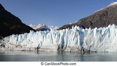Alaska Glacier Bay nature landscape view from cruise ship holiday travel. Global warming and climate change concept with melting glacier with Margerie Glacier and Mount Fairweather Range mountains.