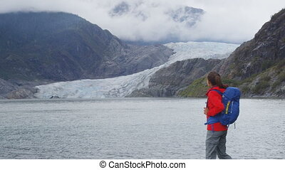 Alaska Tourist walking by Mendenhall Glacier landscape nature near Juneau . Woman hiker on travel adventure hiking wearing backpack. RED EPIC SLOW MOTION.