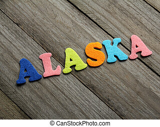 Alaska word on wooden background