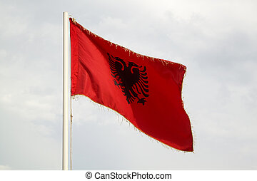 Albanian flag on a blue sky with clouds background