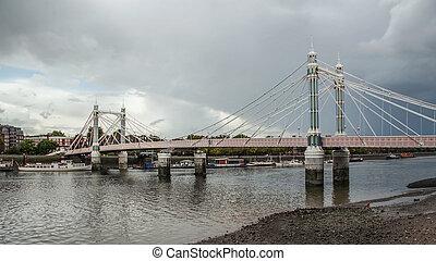 Albert Bridge over river Thames in London on gray overcast ...