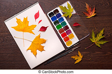 album, paints, brushes and autumn leaves