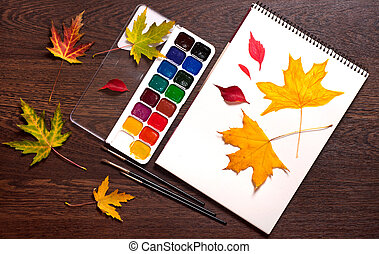 album, watercolor paints, brushes and autumn leaves