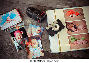Album with children is photos, the ancient camera and a lens on a wooden background