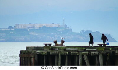Alcatraz Island Tourists - Tourists gather on a pier to view...