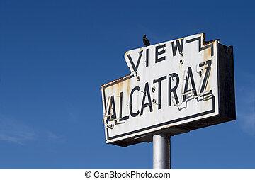 Alcatraz Sign - A bird sits atop a broken old sea-side neon...