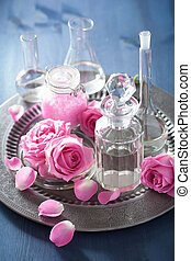alchemy and aromatherapy with rose flowers and chemical...