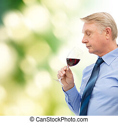 elderly man smelling red wine