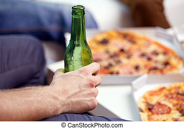 man with beer bottle and pizza at home
