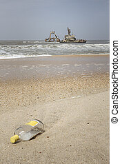 Alcohol bottle in the foreground with a shipwreck on the skeleton coast just outside Swakopmund, Namibia