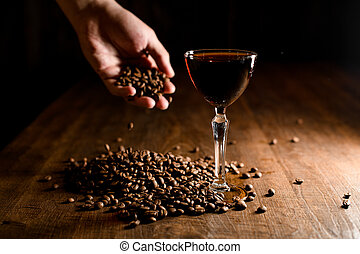 Alcohol drink and hand holding coffee beans