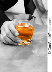 Alcohol - evil! Man's hand holding a glass of whiskey