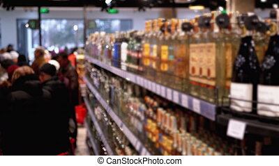Alcohol Sale in Supermarket. Rows and Shelves of Bottled Alcohol in a Store Window in Blur. Buyers Choose Alcoholic Beverages. Wine and Vodka Department. Customers select goods. Choose vodka in the Mall. Close-up
