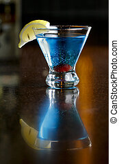 an image of a colourful alcoholic beverage on a restaurant bar countertop.