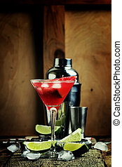 Alcoholic cocktail with watermelon, vodka, syrup, lime juice and ice in a glass. Vintage wooden background with bar tools. Selective focus, shallow depth of field