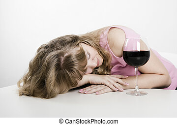 The young woman fallen asleep at a table with a wine glass