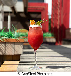 Alcoholic drink. Glass of red tropical cocktail against of sun terrace on blurred background. Vacation concept