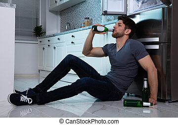 Alcoholic Man Drinking Beer In Kitchen
