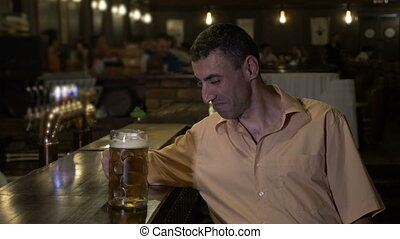 Alcoholic man drinking his sorrow alone at the bar in a pub...