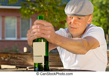Alcoholic man feeling dizzy sitting at a table