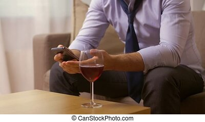 alcoholic with smartphone drinking wine at home -...