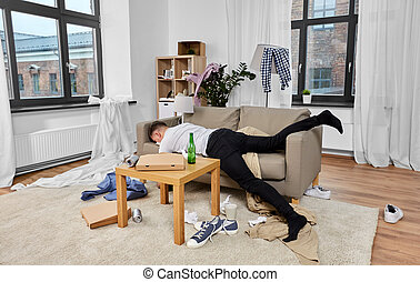 alcoholism, alcohol addiction and people concept - drunk man sleeping on sofa in messy room at home