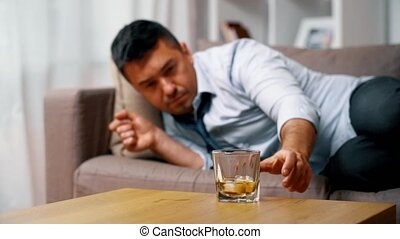 alcoholic lying on sofa and drinking whiskey - alcoholism,...