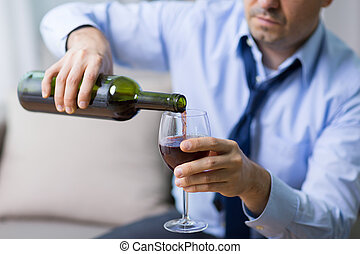 alcoholic pouring red wine to glass at home