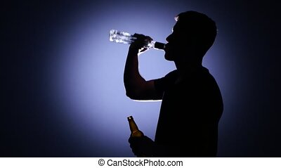 Alcoholism. Back light - Young guy drinking water, and then...