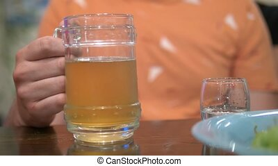 alcoholism concept, close-up, a man holds a beer glass and a glass of vodka