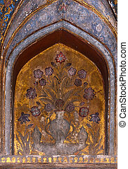 Alcove with golden back ground in blue stones as canvas for a flower composition.