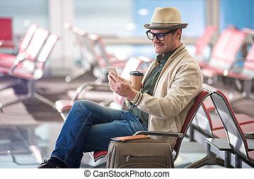 alegre, adulto, viajante, é, segurando telefone móvel