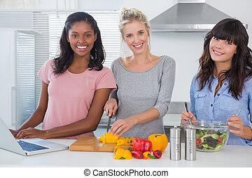 alegre, amigos, elaboración, ensalada, y, usar la computadora portátil, para, receta, mirar cámara del juez, en casa, en, cocina