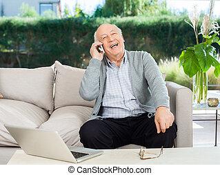 alegre, hombre mayor, responder, smartphone, en, pórtico