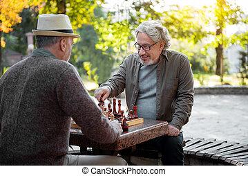 alegre, hombres mayores, jugando al ajedrez, juntos, al aire libre