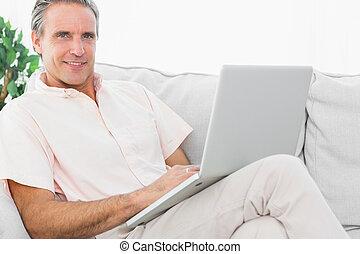 alegre, homem, ligado, seu, sofá, usando computador portátil, olhando câmera