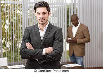 alegre, joven, hombre de negocios, en, formalwear, mantener, armamentos cruzaron