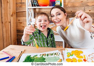 alegre, menino, e, seu, mãe, mostrando, pincéis, câmera