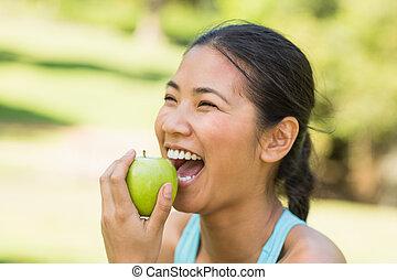 alegre, mujer joven, manzana que come, en el estacionamiento