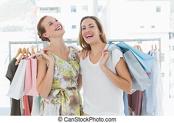 alegre, mujeres, con, bolsas de compras, en, el, tienda ropa