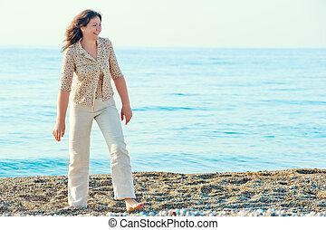 alegre, mulher caminhando, ao longo, a, praia, descalço