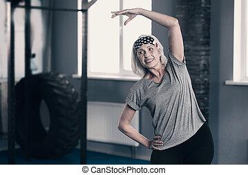 alegre, mulher sênior, fazendo, esticar, em, ginásio