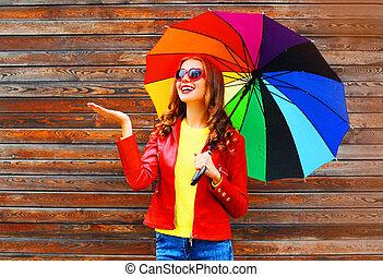 alegre, mulher sorridente, com, coloridos, guarda-chuva, em, dia outono, sobre, madeira, fundo