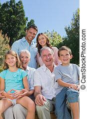 alegre, multi, generación, familia , sentado, en, un, banco, en el estacionamiento
