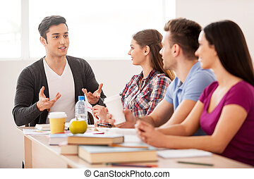 alegre, students., cuatro, alegre, estudiantes, hablar, uno al otro, mientras, sentado, en, el, escritorio