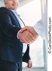 Alert businessman shaking hands with the doctor